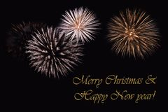 Fireworks on a dark background and a text `Merry Christmas & Happy New year`. Fireworks on a dark background and a text `Merry Christmas & Happy New year` Royalty Free Stock Images