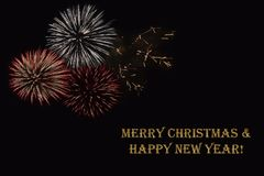 Fireworks on a dark background and a text `Merry Christmas & Happy New year`. Fireworks on a dark background and a text `Merry Christmas & Happy New year` Royalty Free Stock Image