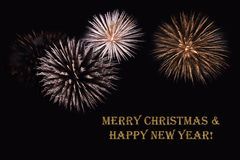Fireworks on a dark background and a text `Merry Christmas & Happy New year`. Fireworks on a dark background and a text `Merry Christmas & Happy New year` Stock Images