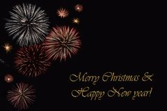 Fireworks on a dark background and a text `Merry Christmas & Happy New year`. Fireworks on a dark background and a text `Merry Christmas & Happy New year` Stock Photo