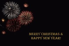Fireworks on a dark background and a text `Merry Christmas & Happy New year`. Fireworks on a dark background and a text `Merry Christmas & Happy New year` Royalty Free Stock Photo