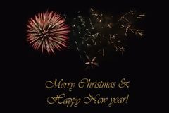 Fireworks on a dark background and a text `Merry Christmas & Happy New year`. Fireworks on a dark background and a text `Merry Christmas & Happy New year` Stock Photos