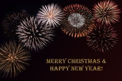Fireworks on a dark background and a text `Merry Christmas & Happy New year`. Fireworks on a dark background and a text `Merry Christmas & Happy New year` Royalty Free Stock Photos