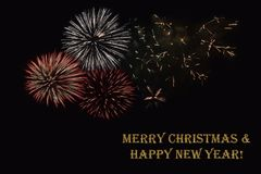 Fireworks on a dark background and a text `Merry Christmas & Happy New year`. Fireworks on a dark background and a text `Merry Christmas & Happy New year` Stock Photography