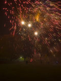 Fireworks display exploding over people and families watching. Portrait view of a firework exploding over families watching from a misty field stock photo
