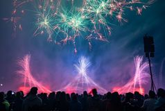 People watching fireworks in night sky stock images