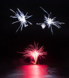 Fireworks display over sea with reflections in water. Fireworks display over sea with bright reflections Royalty Free Stock Photo