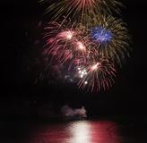 Fireworks display over sea with reflections in water. Fireworks display over sea with bright reflections Stock Photo