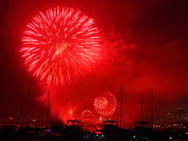 Red blast fireworks display over harbor scenery Royalty Free Stock Image