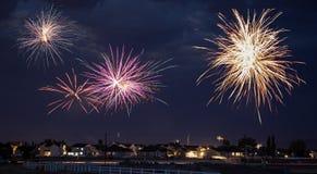 Fireworks explode above a night landscape Stock Photo