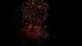 Fireworks explode with multi-colored lights in dark sky. Powerful sparks of festive firecracker illuminate night sky. Amazing festive fireworks explode with stock footage