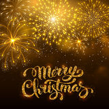 Fireworks. Festive firework bursting in various shapes and golden colors sparkling against black night background. Calligraphy inscription Merry Christmas with Stock Photography