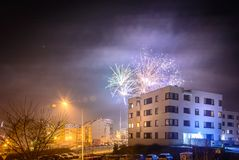 Fireworks firing on New Year`s Eve. City buildings, winter urban landscape Royalty Free Stock Photos