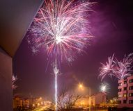Fireworks firing on New Year`s Eve. City buildings, winter urban landscape Royalty Free Stock Photo