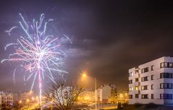 Fireworks firing on New Year`s Eve. City buildings, winter urban landscape Stock Image
