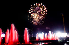 Fireworks and fountains. Beautiful fireworks over colored fountains Stock Image