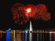 Fireworks with Geneva Fountain. Geneva lake front with fireworks the city lights and the Jet d'Eau in the center Royalty Free Stock Photos