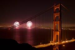 Fireworks and the Golden Gate Bridge. Fireworks in the distance beyond the Golden Gate Bridge at night Stock Photos
