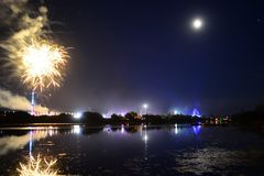 Fireworks at the Isle of Wight Festival. Fireworks, lights and a near full `strawberry` moon reflect off the River Medina on the last night of the 2018 Isle of Stock Photos