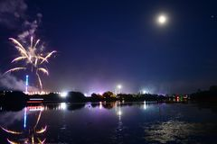 Fireworks at the 2018 Isle of Wight Festival. Fireworks, lights and a near full `strawberry` moon reflect off the River Medina on the last night of the 2018 Isle Stock Images