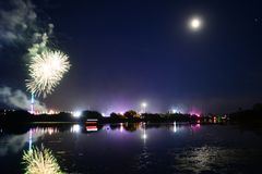 Fireworks Finale at the 2018 Isle of Wight Festival. Fireworks, lights and a near full `strawberry` moon reflect off the River Medina on the last night of the Stock Photo