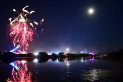 Fairground Rides and Fireworks at the Isle of Wight Festival. Fireworks, lights and a near full `strawberry` moon reflect off the River Medina on the last night Stock Photography