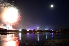 Fireworks Finale at the Isle of Wight Festival 2018. Fireworks, lights and a near full `strawberry` moon reflect off the River Medina on the last night of the Royalty Free Stock Photos