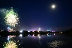 Moon, Fireworks and Fun at the Isle of Wight Festival. Fireworks, lights and a near full `strawberry` moon reflect off the River Medina on the last night of the Stock Photos
