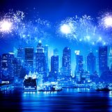 Fireworks in the night sky over New York. A volley of fireworks lights up the sky over Manhattan. The streets and the skyscrapers are shining with lights. The Royalty Free Stock Photo