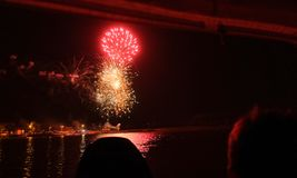 Fireworks at night on the water. Watching the head in the boat Stock Images