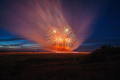 Fireworks over the city. Multi-colored fireworks against the background of the sunset sky. Royalty Free Stock Photos