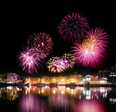 Fireworks over city by the water. Fireworks night over city with calm water reflection stock photography