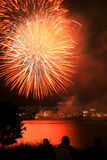 Celebration fireworks. Yellow and red fireworks exploding over a city. They are reflecting in the water and two spectators are enjoying the show Royalty Free Stock Images