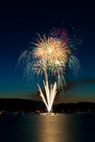 Fireworks over Lake. A bouquet of fireworks exploding from a barge over Lake Coeur d'Alene, Idaho with the reflection showing blurred boats on the water stock image