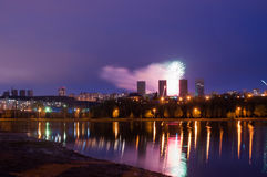 Fireworks over the lake, the city`s night skyline, Stock Photos
