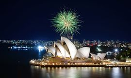 Fireworks over Sydney Opera House bursting into brilliant green display. Sydney, Australia - March 8, 2018 - A big green ball of fireworks bursts against the stock image