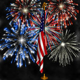 Fireworks over US Flag. Fireworks displayed behind the American Flag on a stand against a night sky stock photos