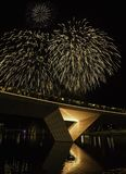Fireworks playing on lighted bridge royalty free stock images
