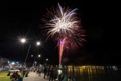 Fireworks popping in the night sky over a harbor royalty free stock image