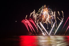 Fireworks reflecting in the water from Forte dei Marmi's Pier Stock Images