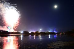 Fireworks and Reflections at the Isle of Wight Festival 2018. Fireworks, lights and a near full `strawberry` moon reflect off the River Medina on the last night Stock Photos