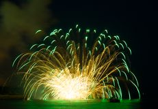Fireworks on the sea. Green and yellow Fireworks over the sea and Reflecting in Water Royalty Free Stock Photography