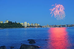 Fireworks shining above city center and reflecting on sea water at blue hour Stock Photo