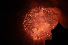 Fireworks And Silhouette. Orange glowing fireworks with silhouette of a building in the lower righthand corner Stock Image