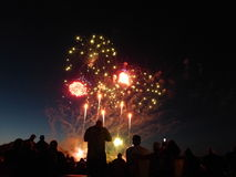 Fireworks with Silhouettes of watchers. Large fireworks display on Independence Day with silhouettes in the foreground of interested onlookers stock images