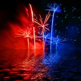 Fireworks in the sky. Background of red and blue fireworks in the sky over water Stock Images