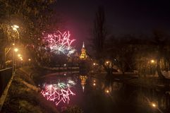 Fireworks. The TimiÈ™oara Orthodox Cathedral with fireworks and Bega river. Night scene with reflection on water royalty free stock photos