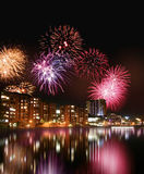Fireworks by the water. Fireworks in the night and colorful city nightline reflecting from water royalty free stock photos