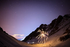 Fireworks on a winter night in mountains Stock Photos