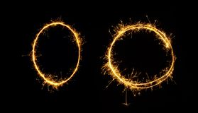 Sparkler oval and circle isolated on black background. Fireworks zero number close up. Burning sparkler in the shape of oval and circle isolated on black stock photography